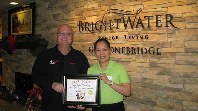 Food Safety 1st, Russell Scott presents Rose Marilou Delos Santos of Brightwater Sr Living the 8,000th Food Safety 1st certificate