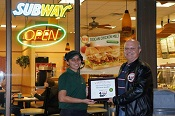 Russell Scott presents Ramneet Sandhu of Subway Restaurant the 4,000th Food Safety 1st certificate.