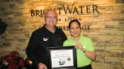 Russell Scott presents Rose Marilou Delos Santos of Brightwater Sr. Living the 8,000th Food Safety 1st certificate.